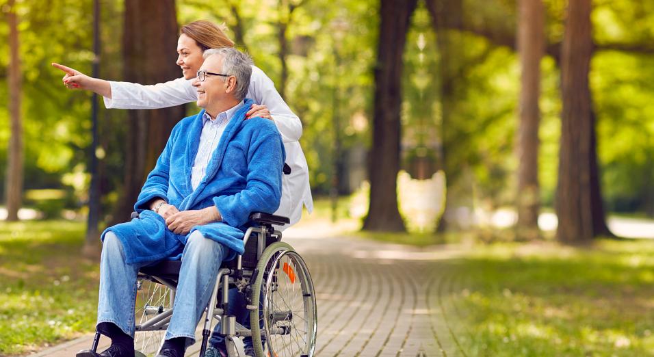caregiver and senior man strolling