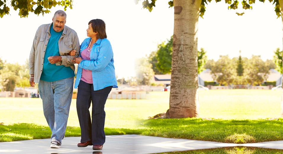 caregiver assisting senior man in walking