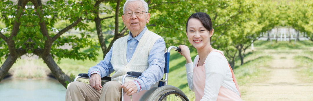 smiling old man with his caregiver walking in the park
