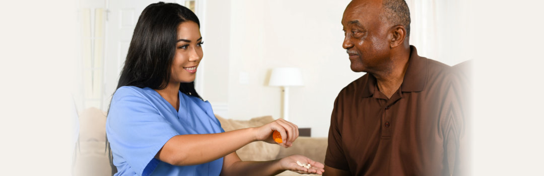 caregiver giving medicine to an old man